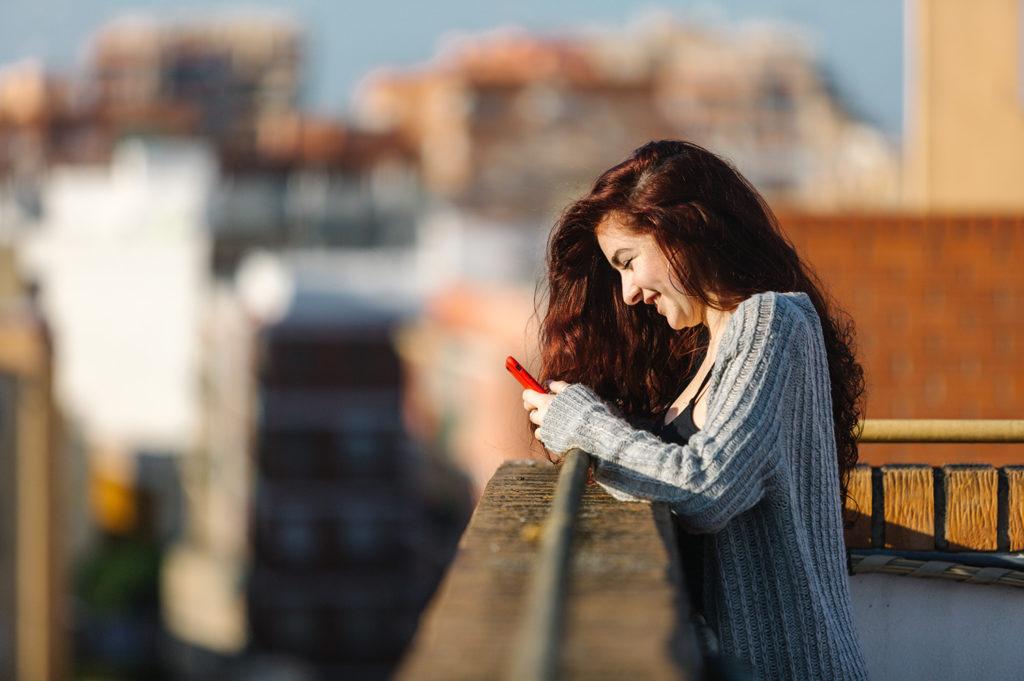 vrouw hangt tegen balkonhek